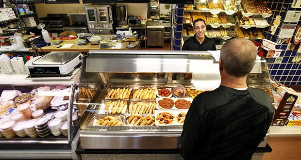 Sam Abed talks with a customer on Oct. 15, 2014 at the Mediterranean Bakery and Deli in Richmond, Va. (AP Photo: Richmond Times-Dispatch, Dean Hoffmeyer)