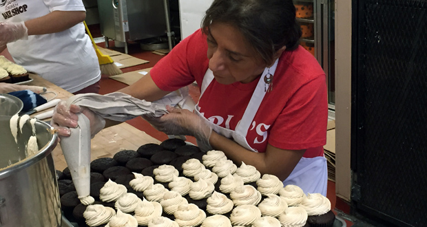 In this photo provided by Carlo's Bakery, Celia Concepcion, who owns bakeries in El Salavador, ices cupcakes Oct. 30 at the bakery in Hoboken, N.J. Concepcion's visit to the U.S. was sponsored by the Business Council for Peace, a program that seeks to boost small businesses, and in turn the economies, of violence-stricken countries. (AP Photo: Carlos' Bakery, Adam Bourcier)