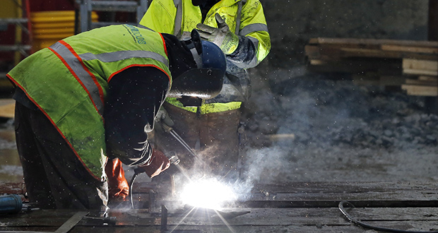 Workers weld at a commercial construction site Monday in Boston. The U.S. economy slowed in the final three months of 2014 as a big burst in consumer spending was offset by weakness in other areas, according to a Commerce Department report released Thursday. (AP Photo: Elise Amendola)