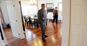Real estate agent Sam Golkar, left, tours a home Jan. 8 being sold by fellow agent Frank Ruan, right, in Cupertino, California. The National Association of Realtors reported Friday that sales of existing homes rose 2.4 percent in December. (AP Photo: Marcio Jose Sanchez)