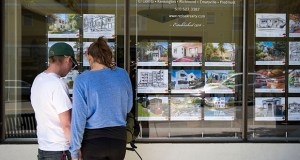 Pedestrians stop to look at flyers listing homes for sale at a realty office in Berkeley, California. Sales of new and existing homes this year probably will gain 5.4 percent to 5.7 million after falling 2.7 percent in 2014, according to Douglas Duncan, chief economist at mortgage giant Fannie Mae in Washington. (Bloomberg News file photo)