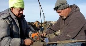"""Efren Hernandez, left, and Kyle Bockin work on the foundation of an apartment complex under construction Jan. 15 on the outskirts of Watford City, North Dakota. Developers are building thousands of housing units in Watford as an alternative to the ramshackle """"man-camps"""" used by many oil field workers. (AP Photo: Matthew Brown)"""