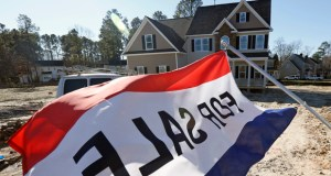 A flag advertising a new home for sale flaps in the breeze Jan. 8 in Richmond, Virginai. The Commerce Department reported Wednesday that sales of new U.S. homes slipped 0.2 percent in January. (AP Photo: Steve Helber)