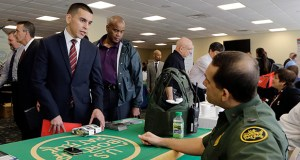 U.S. Marine Corps Veteran Christopher Triana, left, talks about job probabilities Feb. 6 with U.S. Border Patrol agent Frank Miller, right, at the annual Veterans Career and Resource Fair in Miami. The U.S. Labor Department said Thursday that weekly applications for jobless benefits rose to a seasonally adjusted 313,000. (AP Photo: Alan Diaz)