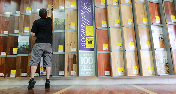 "Kiel Skrobacz, an assistant store manager at Lumber Liquidators in Lutz, Florida, sticks yellow sale tags on products on Thursday. A recent ""60 Minutes"" expose reported the company's Chinese-made laminate flooring contained high levels of formaldehyde, a carcinogen. (AP Photo: Tampa Bay Times, Rachel Crosby)"