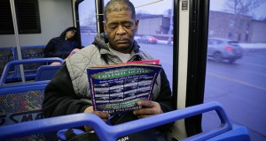 James Robertson, 56, of Detroit looks over ads for used cars Jan. 29 while riding the SMART bus as a part of his commute to work. A Brookings Institution report out Tuesday finds the number of jobs within typical commuting range dropped 7 percent between 2000 and 2012 in major U.S. metropolitan areas. (AP Photo: Detroit Free Press, Ryan Garza)