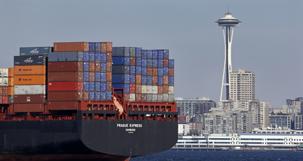 The Space Needle towers in the background beyond a container ship anchored Feb. 15 in Elliott Bay near downtown Seattle. The Commerce Department reported Friday that both exports and imports fell in January. (AP File Photo)
