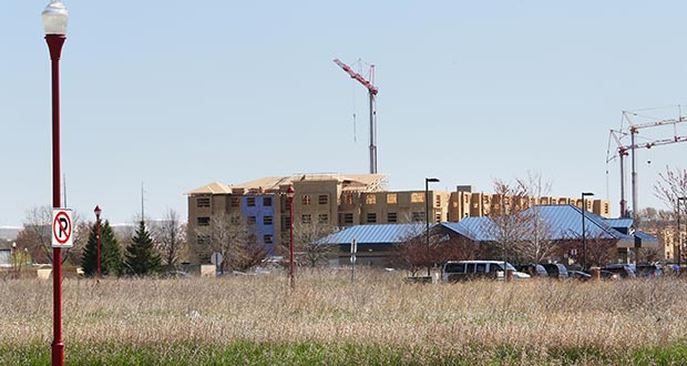 """The city of Apple Valley hopes to draw an office building to a vacant site on Garrett Avenue in close proximity to a station on the Red Line BRT route. In the background, work continues on the 198-unit """"Gabella at Parkside"""" apartments. (Staff photo: Bill Klotz)"""