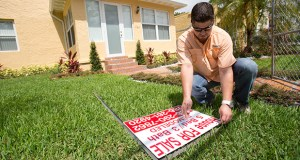 Robert Almirall, director of marketing and special assets coordinator for Mederos & Associates Real Estate Inc., puts up a sign April 24 in front of a home in the Shenandoah neighborhood of Miami. The National Association of Realtors reported Thursday that sales of existing homes fell 3.3 percent last month. (AP Photo:Wilfredo Lee)