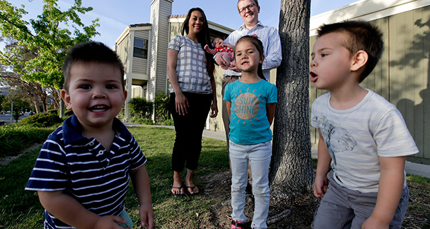Brett Singley, upper right, poses for a picture Monday in front of his townhome with his wife, Angelynn, 28, and children, Isla 5, middle, Isaiah 3, right, Ben, 2, and Aria 1 month, in Santa Clarita, Calif. Singley bought the three-bedroom home for just under $300,000 — $100,000 less than what he was prepared to pay for a house. (AP Photo: Chris Carlson)