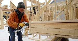 Carpenter Joe Tominc cuts wood for a post Feb. 18 on a new-construction home in Pepper Pike, Ohio. The Commerce Department reported Wednesday that the U.S. economy contracted in the first quart less than previously thought. (AP Photo: Tony Dejak)