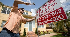 Robert Almirall, director of marketing and special assets coordinator for Mederos & Associates Real Estate Inc., puts up a sign in front of a home April 24 in the Shenandoah neighborhood of Miami. More Americans bought homes in May, the National Association of Realtors reported Monday, a sign of economic strength that is pushing up average prices. (AP file photo)