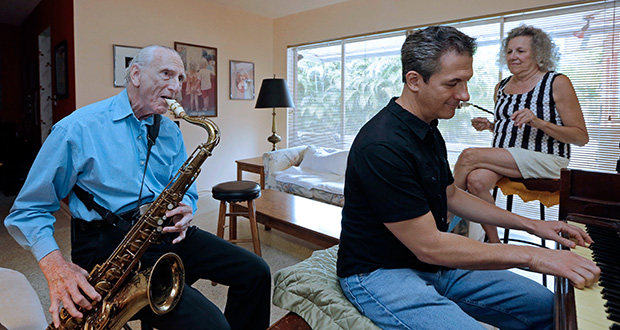 Al Karp, left, plays the saxophone May 11 as he rehearses with his son Larry, center, and wife Saundra, right, at their home in North Miami Beach, Florida. The trio performs old standards locally as the Karp Family to ease stress and help raise money to save their home from foreclosure. (AP Photo: Alan Diaz)