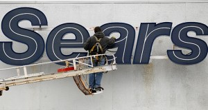 A worker repairs the Sears sign in February 2012 outside the Sears Grand store in Solon, Ohio. Sears Holdings Corp. reported a narrower first-quarter loss on Monday. (AP file photo)
