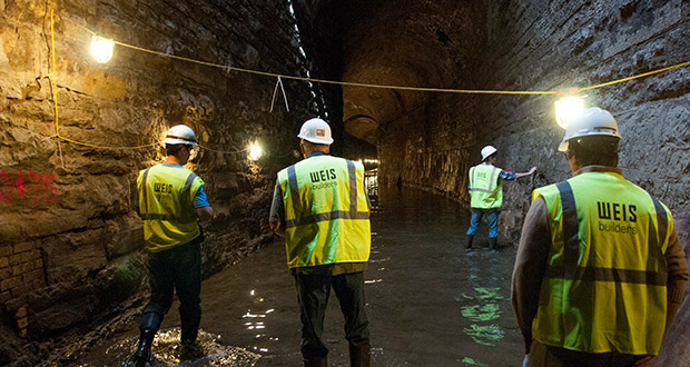 Crews from Weis Builders walk through a tunnel under the A-Mill complex, 301 Main St. SE, where a hydro-electric system will soon be built. The system will serve residents at the A-Mill Artist Lofts. (Submitted  photo: Dominium)