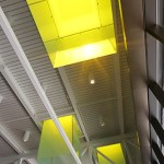 The Walker Library's high ceiling is held up by exposed steel trusses features light-enclosed monitors, which change colors throughout the day from yellow to blue as the sun shifts.