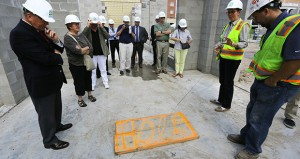 Adolfson & Peterson project manager Carey Everson, second from right, shows visitors where a time capsule will be buried within a walkway that will connect the new Building 21 to the existing Minneapolis Veterans Home campus. (Staff photo: Bill Klotz)