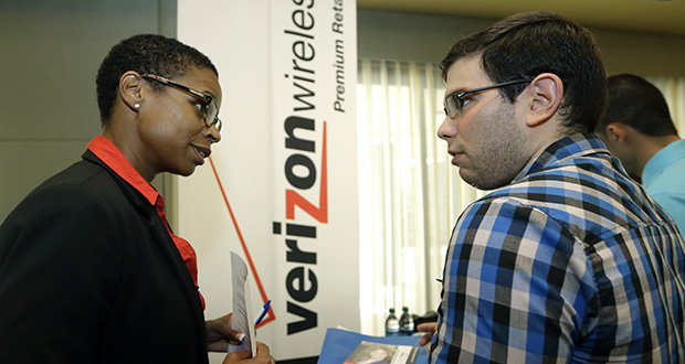 In this July 15 photo, Sasha Vitalis, left, talks about job opportunities with job seeker Omar Delgado at a job fair in Miami Lakes, Florida. Payroll processor ADP said Thursday that companies added 185,000 jobs last month, down from 229,000 in June. (AP photo: Alan Diaz)