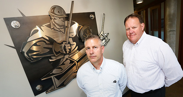 """Chris Grzybowski, partner of Big-D Construction in Minneapolis, and Ken Braun, vice president, stand in their reception area next to the company's """"Iron Man"""" logo. Big-D has seen solid growth in Minnesota since the regional office was established in 2013. (Staff photo: Bill Klotz)"""
