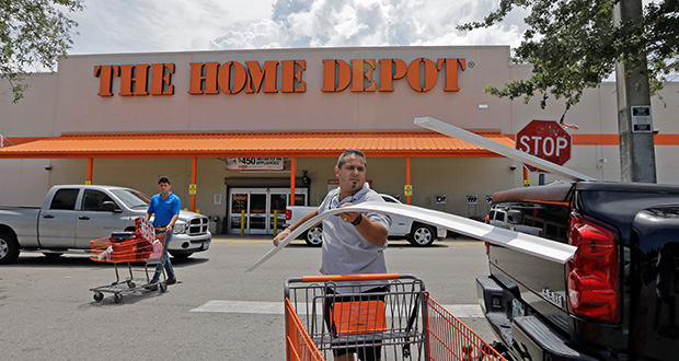 Vicente Aguiar loads garage door trims into his pickup truck July 13 outside a Home Depot in Hialeah, Florida. Home Depot's second-quarter results surpassed Wall Street expectations. (AP Photo:Alan Diaz)