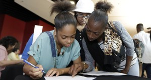 Lashrundra Wilfork, right, helps her daughter, Nala Wilfork, fill out a job application June 10 at a job fair in Sunrise, Florida. The Labor Department reported Wednesday that hiring rose 2.3 percent in June. (AP Photo: Alan Diaz)