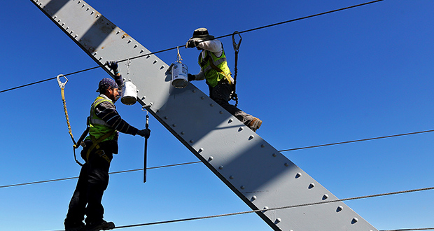 Workers paint the Julien Dubuque Bridge Aug. 24 along U.S. Highway 20 in Dubuque, Iowa. The U.S. government reported Friday that the unemployment rate reached a seven-year low in August. (AP photo: Dave Kettering/Telegraph Herald)