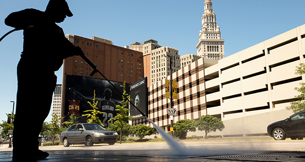 A worker cleans the sidewalk Aug. 5 in front of the Quicken Loans Arena in Cleveland. The Labor Department reported Wednesday that available jobs rose quickly in July. (AP file photo)
