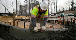 A contractor smooths the concrete on a curb at Skanska USA's Inova Health System construction site in Lorton, Virginia, on Jan. 3, 2013. (Bloomberg News file photo)