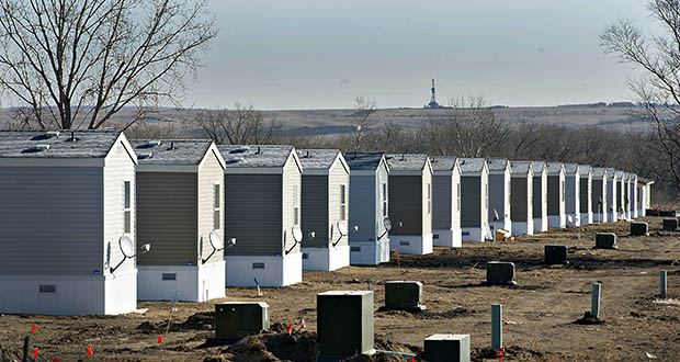 A crude oil drill rig stands on the horizon in February 2012 beyond a row of new single wide mobile homes in Williston, North Dakota. Such camps were supposed to be an interim solution until subdivision and apartment complexes could be built. (Bloomberg file photo)