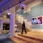 A lobby on the building's skyway level offers a sweeping staircase in front of walls filled by videos showing programs from TPT's four channels and logos and stills from famous shows.