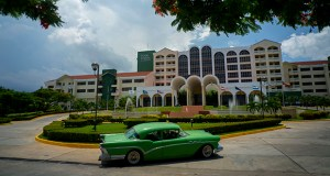 A vintage car passes in front of the Four Points by Sheraton hotel Tuesday in Havana. American hotel giant Starwood has begun managing this hotel run by the Cuban military, opening one of the biggest holes in the U.S. trade embargo on Cuba since Presidents Barack Obama and Raul Castro declared detente in Dec. 2014. (AP Photo: Ramon Espinosa)