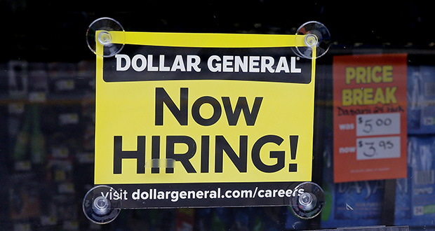 "A ""Now Hiring"" sign hangs May 18 in the window of a Dollar General store in Methuen, Massachusetts. (AP file photo)"