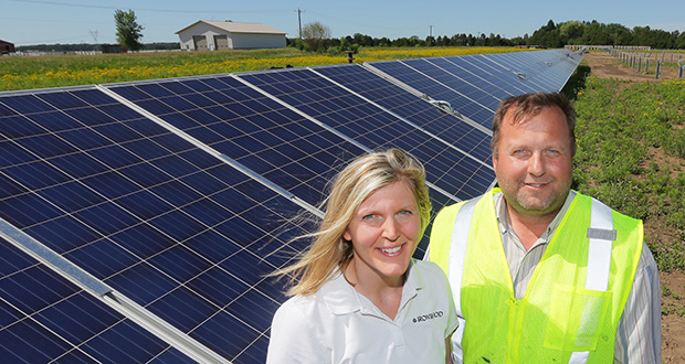 Randy and Jody Swanson's Ironwood Contracting is benefiting from Minnesota's booming renewable-energy market. In this photo, the Swansons stand with a solar array that is part of an 800-acre project near North Branch. (Staff photo: Bill Klotz)