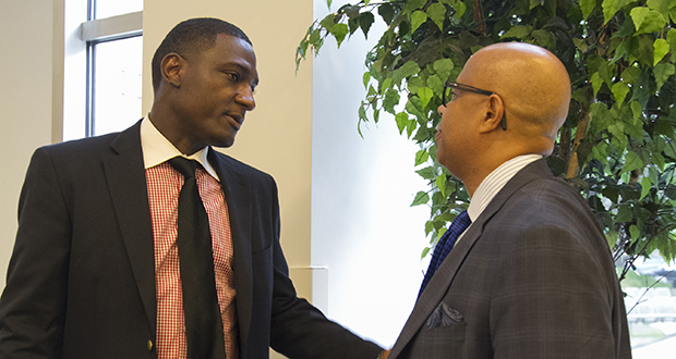 Ambrose Kpoto (left), founder of Burnsville-based Future Generation Medical, talks with Gary Cunningham, CEO of the Metropolitan Economic Development Association, during a breakfast roundtable Tuesday. (Staff photo: Matt M. Johnson)