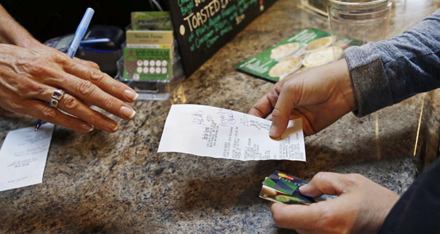A customer buys lunch Sept. 28 at Smolak Farms in North Andover, Massachusetts. The Commerce Department reported Friday that U.S. economic growth surged in the third quarter despite slowed consumer spending. (AP Photo: Elise Amendola)