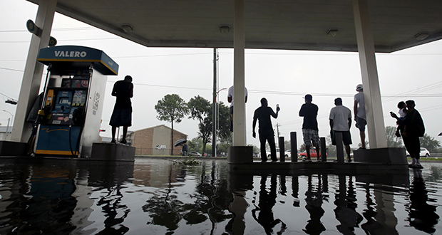 People watch heavy rain from the relative safety of a flooded gas station caused by Hurricane Harvey on Sunday in Houston. The remnants of the storm sent devastating floods pouring into Houston as rising water chased thousands of people to rooftops or higher ground. (AP Photo: Charlie Riedel)