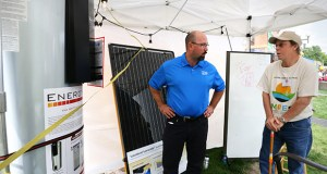 "Jeff Haase, of Great River Energy, displays an 80-gallon electric water heater in the Minnesota Renewable Energy Society booth at the Minnesota State Fair in Falcon Heights. In a program known as ""community storage,"" customers can reduce their bills by installing electric water heaters that Great River Energy then controls, heating them between 11 p.m. and 7 a.m. (Staff photo: Bill Klotz)"