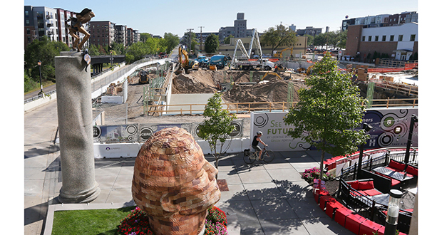Foundation construction for the eight-story MoZaic East at 2900 Fremont Ave S. in Minneapolis can be seen across an art-filled park built by The Ackerberg Group during the first phase of the project in 2012. (Staff photo: Bill Klotz)