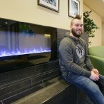 Property Manager Jake LaFaive in the lobby with a fake fireplace.