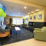People sit in the lobby off the main entrance for the Hawthorne EcoVillage Apartments. Amenities in the apartment building include a patio with grills, underground parking, and community and fitness rooms.