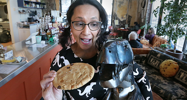 Tina Rexing, owner of the T-Rex Cookie Co., has a lighthearted moment with a dinosaur friend in her shop at 3338 University Ave. SE in Minneapolis. (Staff photo: Bill Klotz)