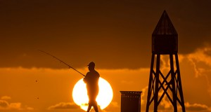 A fisherman prepares to cast a line July 14, 2016, as the sun rises behind him as he fishes off a jetty into the Atlantic Ocean, in Bal Harbour, Florida. If Sunshine State legislators get their way, Florida's time may never fall back after daylight saving time happens this weekend. By overwhelming, bipartisan majorities, the normally fractious Senate and House agreed this week to make Florida the first in the nation to adopt year-round daylight saving time statewide. (AP file photo)