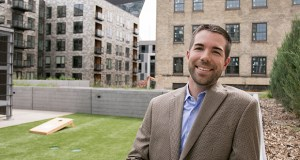 Shane LaFave stands on an amenity deck at Sherman Associates' East End apartments at 721 Washington Ave. S. in downtown Minneapolis. The Thresher Square building – which Sherman is renovating into a hotel – is in the background. (Staff photo: Matt Johnson)