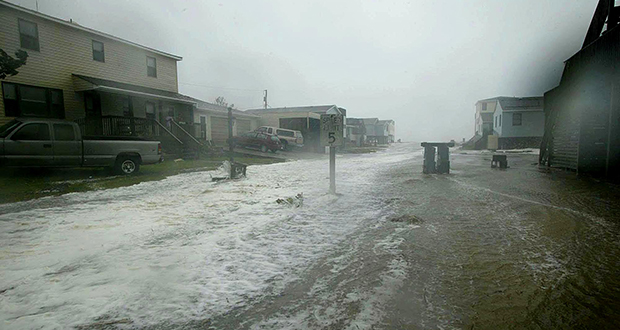 In this Sept. 18, 2003, photo, the sea surges over Beach Road in Nags Head, North Carolina, as hurricane Isabel hits the coast. According to county records, Nags Head beaches have routinely received sand from beach nourishment programs, which has helped increase the value of homes in the city compared to other beach communities in North Carolina. (Bloomberg file photo)