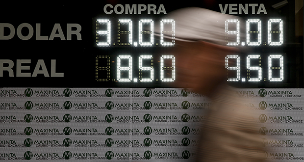 A man walks past a sign announcing the price of U.S. dollar and Brazilian real, in exchange for Argentine pesos, at an exchange house in Buenos Aires, Argentina on Monday. Argentina's President Mauricio Macri has announced new taxes on exports and the elimination of several ministries on Monday in a bid to halt economic turmoil that has sent the peso to record lows. (AP Photo: Natacha Pisarenko)