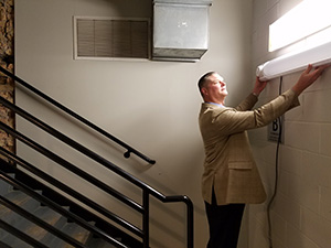 Erik Ennen, facilities services manager with Minneapolis-based Center for Energy and Environment, shows a new LED fixture with an energy-saving sensor on the end. (Submitted photo)