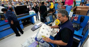 Walmart reported Thursday its best sale performance at its established U.S. namesake stores for the fiscal first quarter in nine years. In this Nov. 9, 2018, photo, Walmart associate Javaid Vohar, right, checks out customers at a Walmart Supercenter in Houston. (AP file photo)