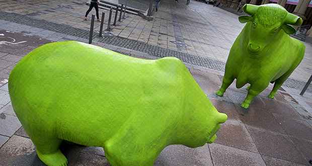 "The bull and bear in front of the stock market in Frankfurt, Germany are painted green June 3 to celebrate ""Green Sauce"" week in the city. The European Central Bank announced steps on Thursday it hoped would bolster the eurozone economy. (AP Photo/Michael Probst)"