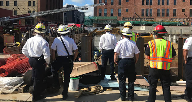 Emergency responders look, July 29, 2019, on as a trapped construction worker is rescued Monday from a project site at 240 Park Ave. S. in downtown Minneapolis.