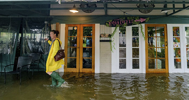 In this July 13 photo, Aimee Cutter, the owner of Beach House restaurant, walks through water surge from Lake Pontchartrain on Lakeshore Drive in Mandeville, Louisiana, ahead of Hurricane Barry. A standard business insurance policy will cover losses from hurricane wind damage like broken windows and roofs that are torn away. (AP file photo)